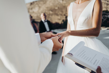 Bride and groom in light summer clothes hold each other hands during the ceremony