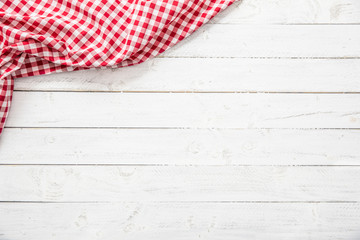 Red checkered kitchen tablecloth on wooden table. Wall mural