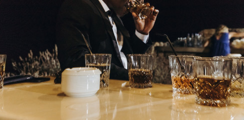 Glasses with whisky stand on the table before man in classy black suit