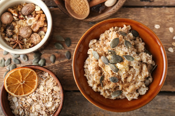 Bowls with tasty oatmeal and nuts on wooden table