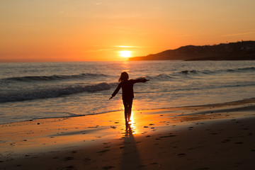 Happy child running on the beach during sunset, Praia da Luz, Algarve, Portugal