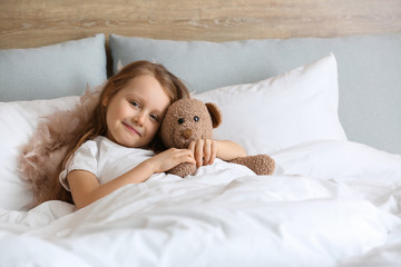 Cute little girl with toy bear in bed