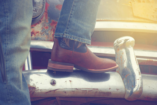 Cowboy boots and a rusty car, car,