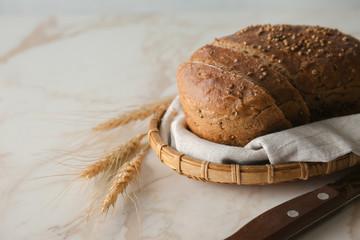 Loaf of fresh bread on light background