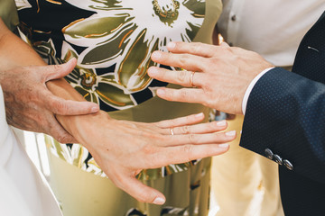 Old lady in green dress holds bride's hand tender