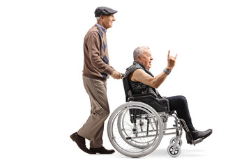 Elderly man pushing a man making a rock and roll hand sign in a wheelchair