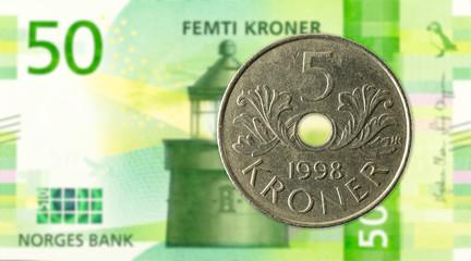 5 norwegian krone coin against 50 new norwegian krone banknote
