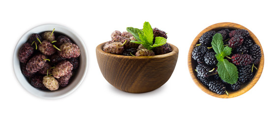 Mulberries in a wooden bowl with copy space for text. Black and purple mulberry on white background. Ripe and tasty mulberry isolated on white background. Top view. Set of mulberries of bowls.