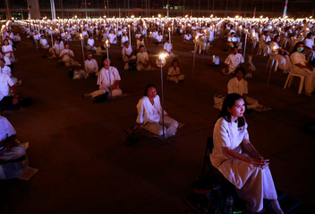 Devotees pray at the Wat Phra Dhammakaya temple during a ceremony to commemorate Makha Bucha Day outside Bangkok