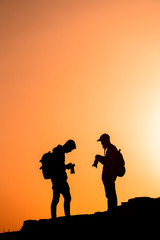 Photographers who shoots a sunset in the mountains