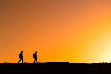 People silhouettes walking over mountain
