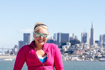 Portrait of a woman in front of the San Francisco skyline, as seen from the water in the bay. Wind blown hair