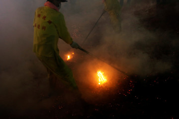 A worshipper extinguishes burning firecrackers during the night procession of the Tudigong, a tutelary deity, to celebrate the traditional Lantern Festival, marking the end of the Chinese Lunar New Year celebrations in Taipei