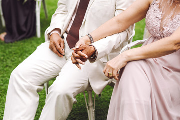 Man in white suit and lady in pink dress hold each other hands sitting on the chairs during the ceremony