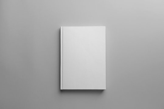 Book with blank cover on light background