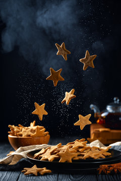 Falling stars shaped cookies with powdered sugar. Vertical composition on a dark background