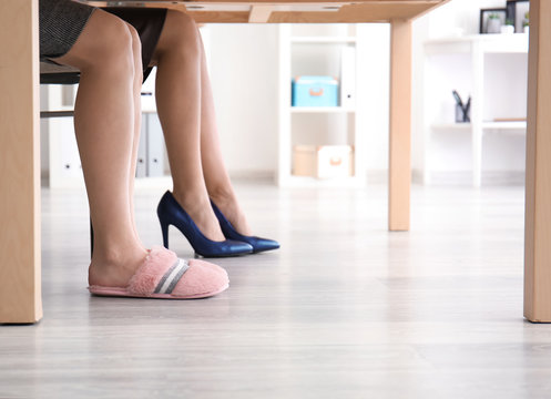 Young women in slippers and high heeled shoes working in office
