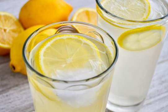 Two glasses of lemonade on a wooden surface