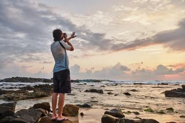 A young man photographs the sunset.