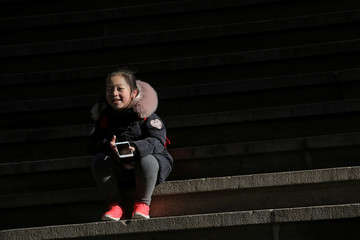 A child uses a smartphone on Wall St. during the morning commute in New York