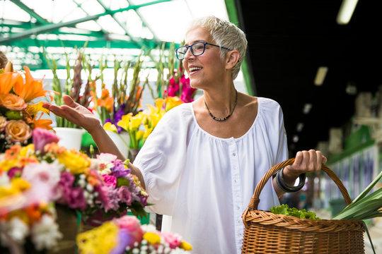 Charrming senior woman buying  flowers on  market