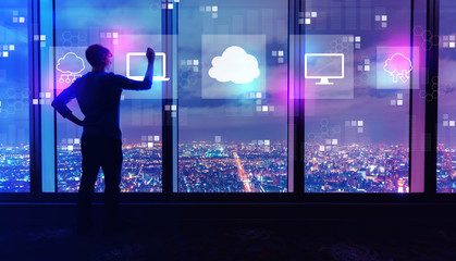 Cloud computing with man writing on large windows high above a sprawling city at night