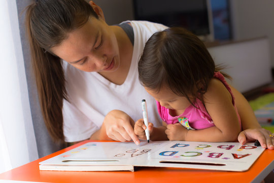A mother teaching her child how to write the alphabets. homeschooling concept. Kids focusing and concentrating.