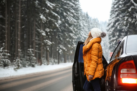 Young woman near car at winter resort