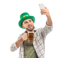 Handsome young man in green hat and with mug of beer taking selfie on white background. St. Patrick's Day celebration