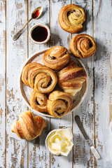 Variety of homemade puff pastry buns cinnamon rolls and croissant served with jam, butter as breakfast over white plank wooden background. Flat lay, space