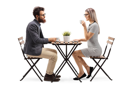 Young man and woman drinking coffee at a table