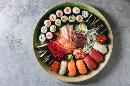 Sushi Set nigiri sashimi and sushi rolls in ceramic serving plate with salad over grey concrete background. Flat lay, space. Japan menu