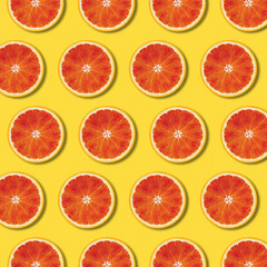 Red orange slices pattern on yellow color background. Minimal flat lay top view food texture