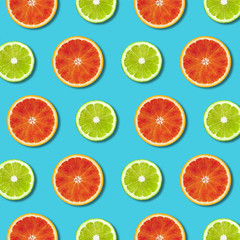 Vibrant red orange and green lime lemon slices pattern on turquoise background