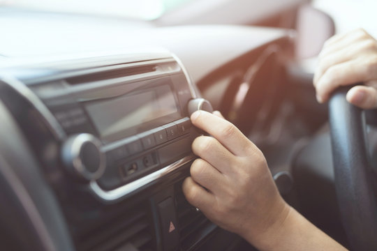 close up hand open car radio listening. Car Driver changing turning button Radio Stations on His Vehicle Multimedia System. Modern touch screen Audio stereo System. transportation and vehicle concept