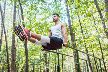 Fit man doing abdominal exercises in forest outdoor gym