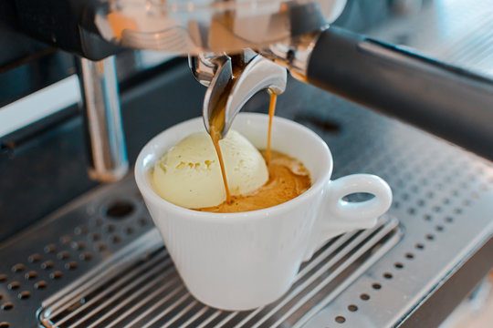 Affogato coffee with ice cream on a ceramic cup with coffee pouring from espresso machine