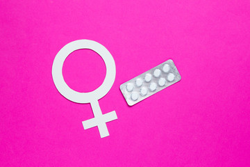 Women Health. Female gender symbol, pills on pink background.
