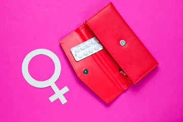 Women Health. Female gender symbol, pills in red purse on pink background.