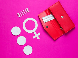 Women Health. Products for feminine hygiene, self-care, female gender symbol on pink background. Ear sticks, pads, pills in purse. Top view