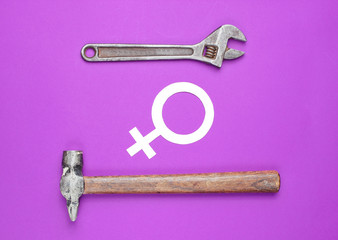 Women choose male work. Feminism. Gender equality. Hammer, wrench, symbol of feminist on purple background. Top view