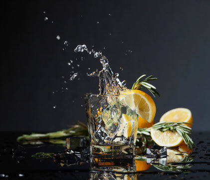 Cocktail gin-tonic with lemon slices and twigs of rosemary.