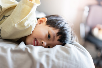 A kid is playing in the morning while watching TV in the bed in the bedroom.