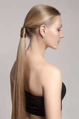 woman with a hair tail. Clean skin of the face. Blonde. Gray background