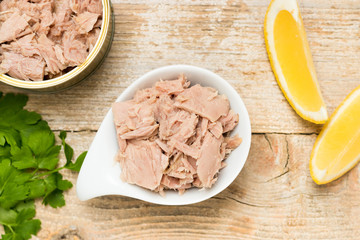 Premium quality canned tuna in a white bowl with lemon and another opened tuna can. Close up of a high quality preserved sea food.