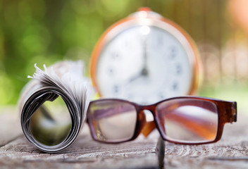 Morning news concept - newspaper and eyeglasses with alarm clock in the background