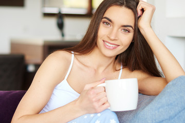 Beautiful young woman holding mug in her hand while relaxing on sofa at home
