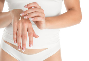 Woman applying hand cream, white background, closeup