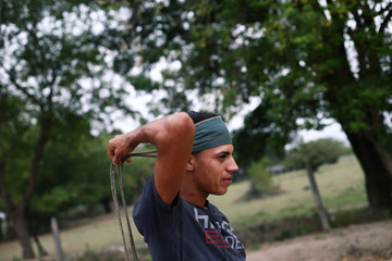 Luis, a Venezuelan working as 'Maletero', ties a rope on his head for loading merchandise, on the outskirts of Cucuta