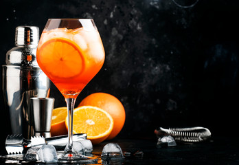 Aperol spritz cocktail in big wine glass, summer Italian low alcohol cold drink, dark bar counter background with tools, summer mood concept, selective focus